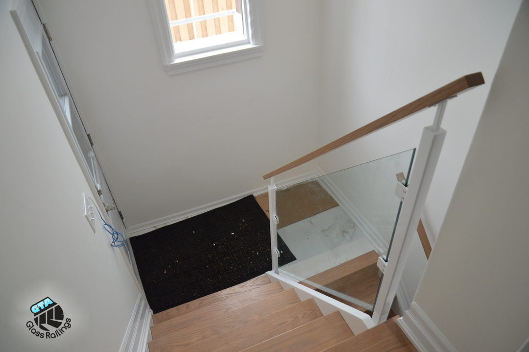 indoor glass railing with wood handrail